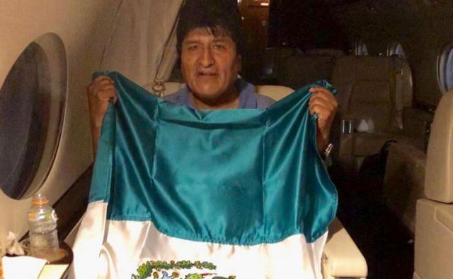 Evo Morales z mehiško zastavo na letalu, ki ga je zanj v La Paz poslala Mehika. FOTO: Reuters