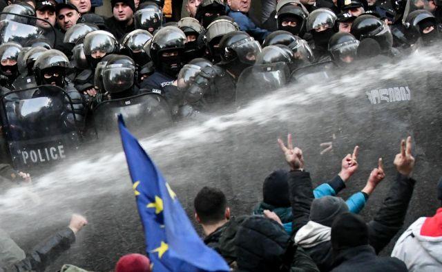 Na protestih v Tbilisiju, na katerih je več deset tisoč ljudi protestno zahtevalo predčasne volitve, je policija ouporabila vodne topove in solzivec. Aretiranih je bilo več deset protestnikov. FOTO: Vano Shlamov/Afp