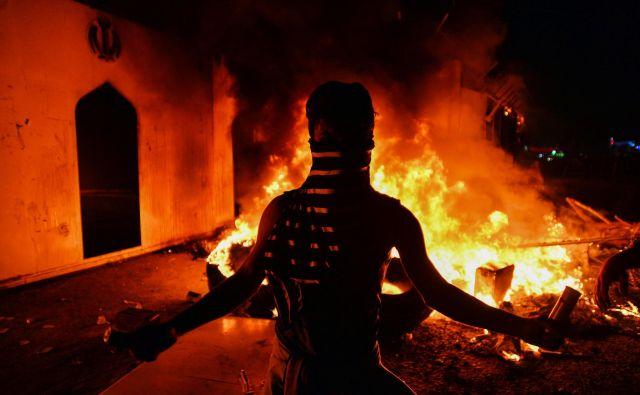 Protestnik pred gorečim konzulatom. FOTO: AFP<br />