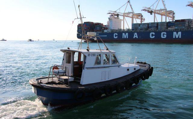 Pomorski pilot se vkrca na ladjo, do katere se pripelje s čolnom, in jo pomaga varno pripeljati v pristanišče. Foto Piloti Koper