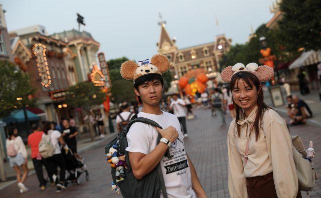 Navdušena turista v hongkonškem Disneylandu. FOTO: Reuters