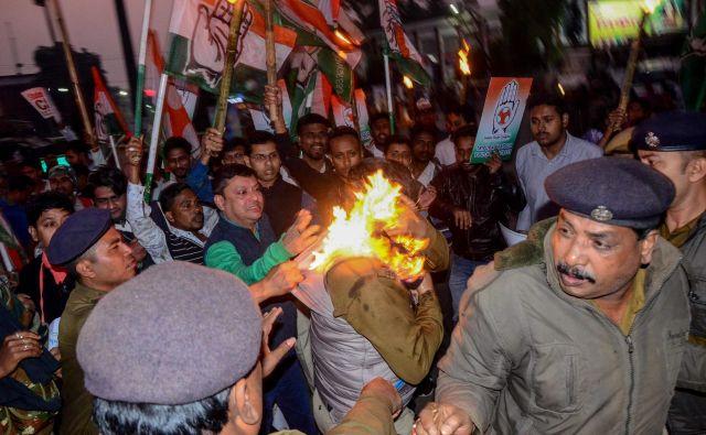 Policisti poskušajo rešiti policista, ki ki ga je zajel ogenj med protestom proti vladnemu predlogu zakona o državljanstvu (CAB) v Agartali, glavnem mestu indijske severovzhodne države Tripura. Spremenjeni zakon predvideva indijsko državljanstvo za prišleke iz Afganistana, Bangladeša in Pakistana, ki pripadajo »preganjanim manjšinam«. FOTO: Arindam Dey/Afp