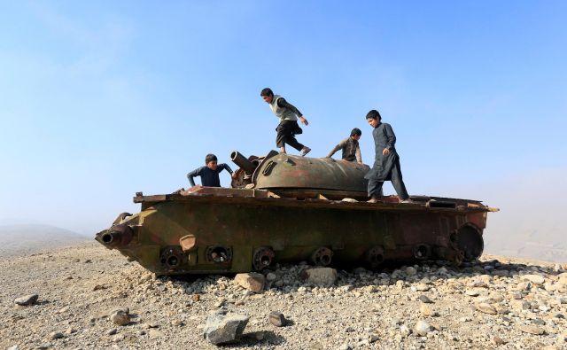 Otroci se igrajo na zapuščenem ruskem tanku. FOTO: Reuters