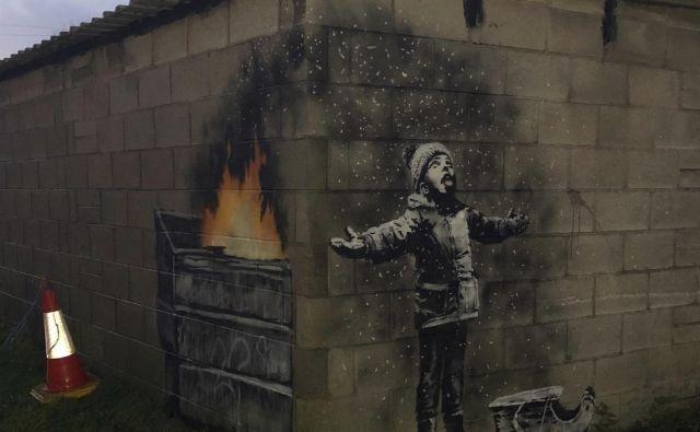 Deček se na videz idilično predaja igri snežink, v resnici pa nanj pada pepel iz gorečega zabojnika, ob katerem se pokuša ogreti. Foto AP