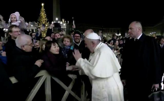 Jože Debevc: »Ko se je papež Frančišek podal med množico, ga je ena od teh prijela za roko in ga nekoliko povlekla k sebi. Njegova reakcija je bila hitra in sunkovita: prav nič nežno jo je udaril po njeni iztegnjeni roki.« Foto Reuters