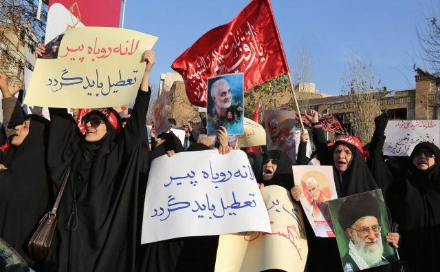Protest s podobami Kasema Sulejmanija in ajatolaha Alija Kameneja pred britanskim veleposlaništvom v Teheranu. FOTO: Atta Kenare/AFP