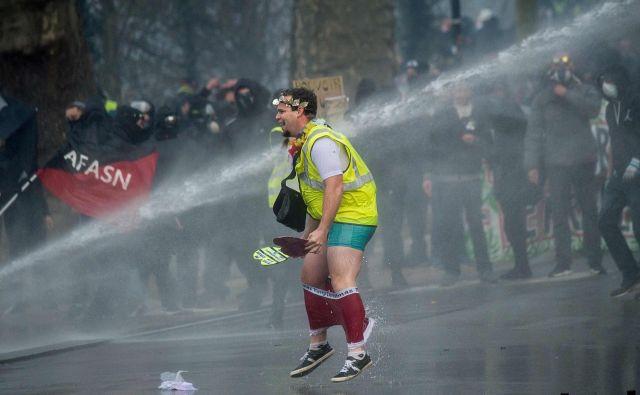 Člana francoskega protivladnega gibanja Rumeni jopiči je v francoskem mestu Nantes namočil policijski vodni top, med stavko zaradi vladne pokojninske reforme. FOTO: Loic Venance/Afp<br />