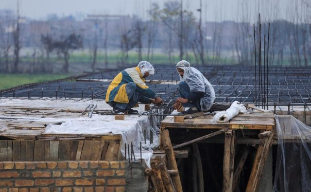Delavci na prostem so toploto iskali v plastičnih palerinah. FOTO: Fayaz Aziz/Reuters