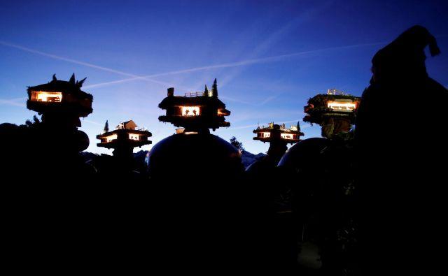 V vasici Urnaesch na severvzhodu Švice moški oblečeni kot figure »Chlaeuse«, med tradicionalnim obredom Sylvesterchlausen, plašijo zle duhove. Tradicionalna oprava je sestavljena iz osvetljenih klobukov in okroglih kravjih zvoncev. FOTO: Arnd Wiegmann/Reuters