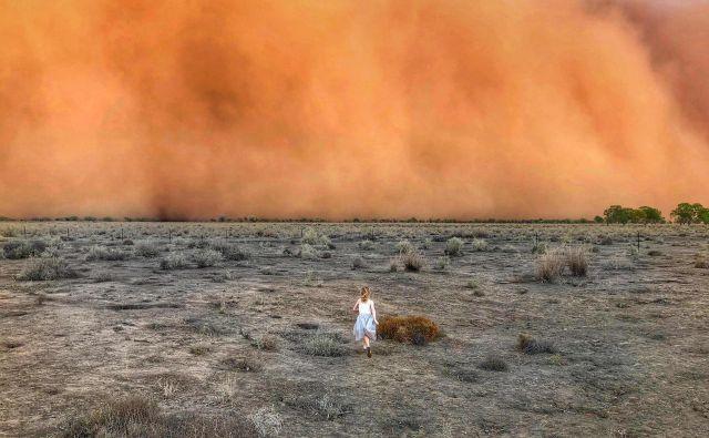 Deklica teče proti peščeni nevihti v avstralskem mestu Mullengudgery v Novem Južnem Walesu. Peščena nevihta je prizadela številne dele zahodnega Novega Južnega Walesa v Avstraliji, kjer se večmesečna suša nadaljuje. FOTO: Handout/Afp<br />
