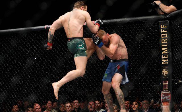 Irski zvezdnik mešanih borilnih športov Conor McGregor se je po dobrih 15 mesecih premora v šampionskem slogu vrnil v kletko. Na spektaklu združenja UFC 246 v nabito polni lasvegaški areni T-Mobile je uprizoril pravi »blitzkrieg«, saj je že po pičlih 40 sekundah s tehničnim nokavtom strl odpor Američana Donalda Cerroneja. FOTO: Steve Marcus/Afp