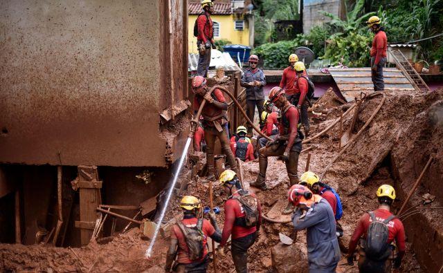 Blato morajo odstranjevati z novo vodo, da lahko pridejo do morebitnih preživelih v stavbah. FOTO: Afp