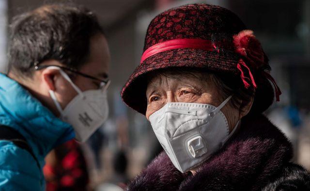 Kitajci so že pred dnevi potrdili, da se virus prenaša med ljudmi, a glavni izvor izbruha so domnevno živali. Za izhodišče virusa trenutno opredeljujejo veletržnico z živimi ribami in drugimi živalmi v Wuhanu. FOTO: Nicolas Asfouri/AFP