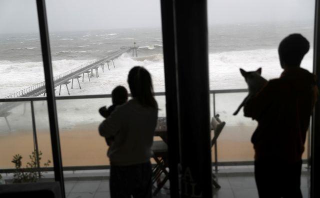 Družina opazuje razjarjeno morje zaradi nevihte Gloria, ki je zajela španska obalna mesta. FOTO: Reuters/Nacho Doce