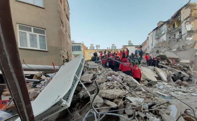 Mediji so objavili posnetke, na katerih je videti, kako več deset reševalcev v tišini išče preživele na vrhu večnadstropne stavbe, ki se je zrušila. FOTO: Ali Haydar Gozlu/AFP