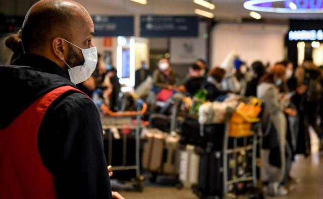 Potnike iz Kitajske na največjem pariškem letališču so včeraj takole sprejemali letališki uslužbenci, opremljeni z maskami. Foto AFP