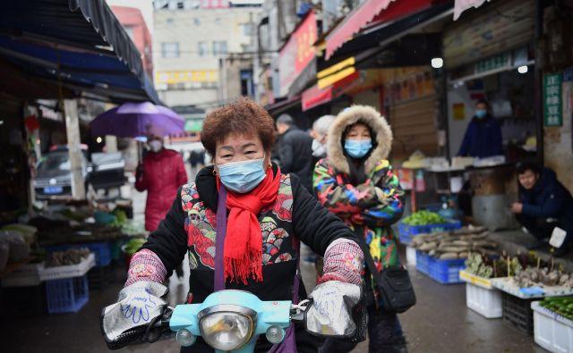 V Wuhanu se je zbrala smetana visokih in novih tehnologij ter njihove podružnice, ki se ponašajo s predpono bio-, zato ni naključje, da se širijo govorice, da je virus ušel iz enega od tamkajšnjih laboratorijev. Na fotografiji prebivalka med vožnjo skozi mestno tržnico. FOTO: AFP