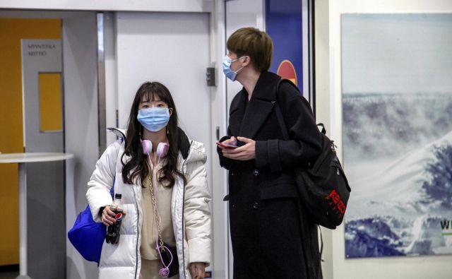 Potniki iz Kitajske nosijo zaščitne maske ob prihodu na letališče na Finskem. FOTO: Reuters