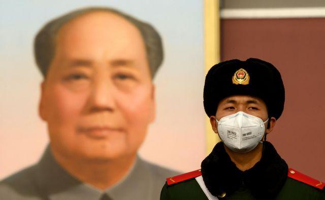 Nošenje maske je obvezno tudi za stražarja pred portretom Maa Zedonga v Pekingu. FOTO: Noel Celis/AFP