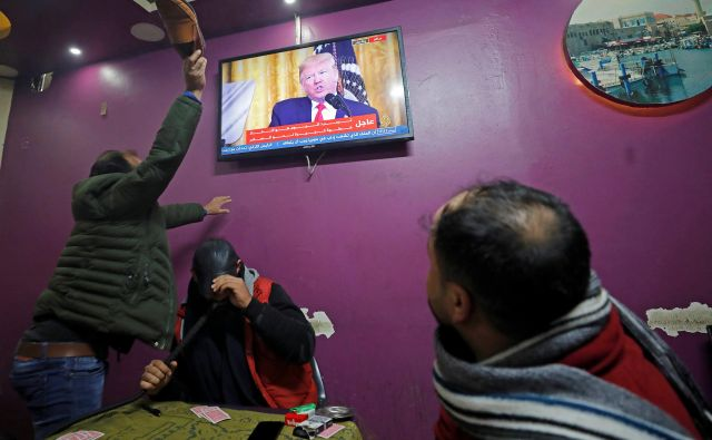 Jezni Palestinec s čevljem udarja po televizijskem zaslonu, med predvajanjem ameriškega mirovnega načrta Donalda Trumpa v kavarni v Hebronu, na izraelskem okupiranem Zahodnem bregu. FOTO: Mussa Issa Qawasma/Reuters