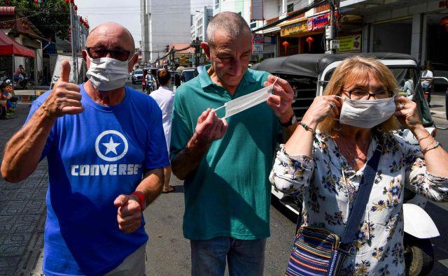 Strah pred novim virusom se širi po Aziji. Na fotografiji so turisti z zaščitnimi maskami v glavnem mestu Kambodže Phnom Penhu, kjer so ta teden uradno potrdili prvi primer okužbe. FOTO: AFP