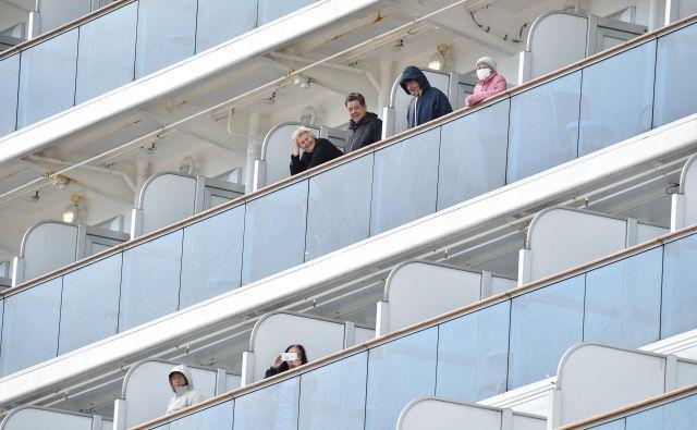 Potniki na krovu križarkeDiamond Princess ob prihodu v pristanišče Jokohama. FOTO: Kazuhiro Nogi/AFP