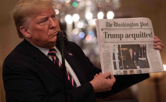 Predsednik Trump razkazuje časopis z naslovnico o oprostitvi. Foto Nicholas Kamm Afp