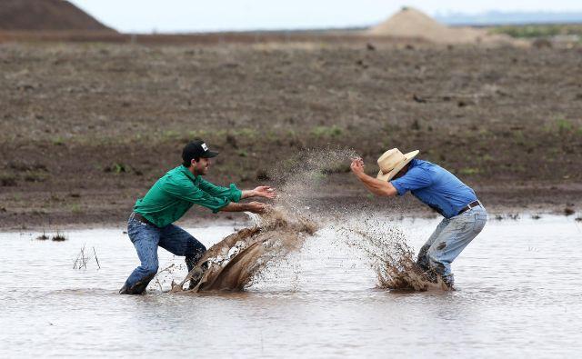 Soseda s kmetij v Liverpool Plains v Novem južnem Walesu James Purshouse (levo) in Jock Tudgey se veselita obilnega dežja, ki je končal triletno sušo in omejil nekaj mesecev trajajoče požare. FOTO: Stringer/Reuters