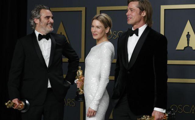 Joaquin Phoenix, Renee Zellweger in Brad Pitt pozirajo z zlatimi kipci. FOTO: Lucas Jackson/Reuters