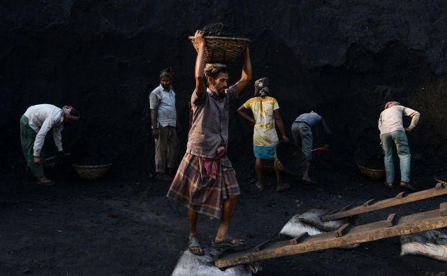 Delavec nosi premog s tovorne ladje na tovornjak v pristanišču na obrobju Dake. FOTO: Munir Uz Zaman/AFP