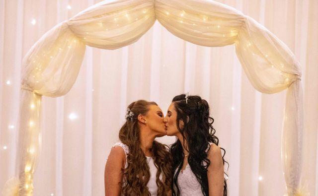 V Carrickfergusu, severno od Belfasta, sta se kot prvi istospolni par na Severnem Irskem poročili tamkajšnji dekleti Robyn Peoples in Sharni Edwards, takoj po spremembi zakona, ki je stopil v veljavo 10. februarja. FOTO: Paul Faith/Afp<br />