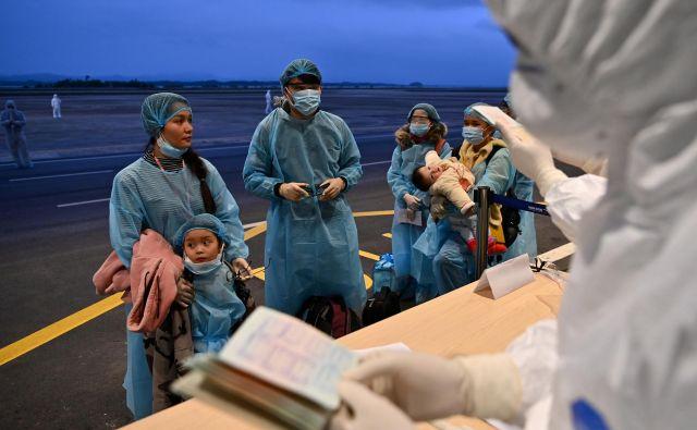 Vietnamce, ki so se vrnili iz Wuhana, epicentra novega koronavirusa, so na letališču temeljito pregledali. FOTO: Reuters