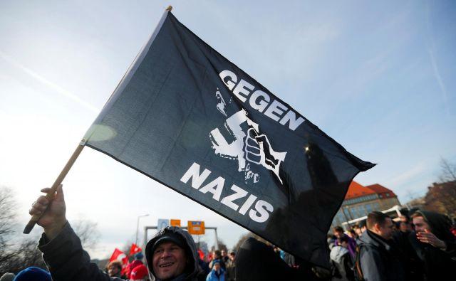 Protestnik z zastavo 'proti nacistom'. FOTO: Hannibal Hanschke/Reuters