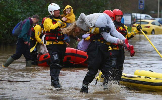 Pripadniki reševalnih služb evakuirajo prebivalce in njihove pse iz poplavljenih hiš z reševalnimi čolni, potem ko je reka Taff prestopila bregove v Nantgarwu, na jugu Walesa. Veliko Britanijo je konec tedna zajela nevihta Dennis s silovitim vetrom in nalivi, ki so povzročili poplave. Oblasti so razglasile nevarnost poplav v več kot 300 krajih, še posebej kritično je na jugu Walesa. FOTO: Geoff Caddick/Afp<br />