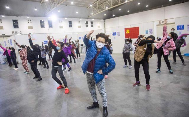 Bolniki z blažjimi simptomi koronavirusa v wuhanskem razstavišču, ki je spremenjeno v začasno bolnišnico. FOTO: AFP