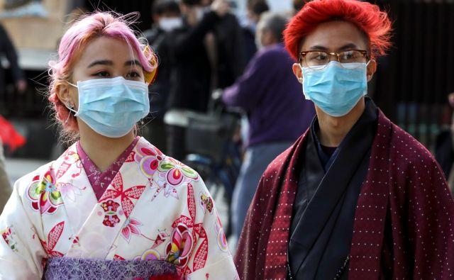 Turisti z maskami v japonski prestolnici. FOTO: Athit Perawongmetha/Reuters