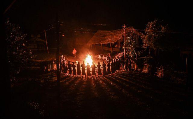 Članice plemena Gongwang Bonyo, ki so med najbolj izoliranimi skupnostmi v Burmi, med celonočnim obredom plešejo ob tabornem ognju, da bi blagoslovili prihodnjo letino. FOTO: Ye Aung Thu/Afp<br />