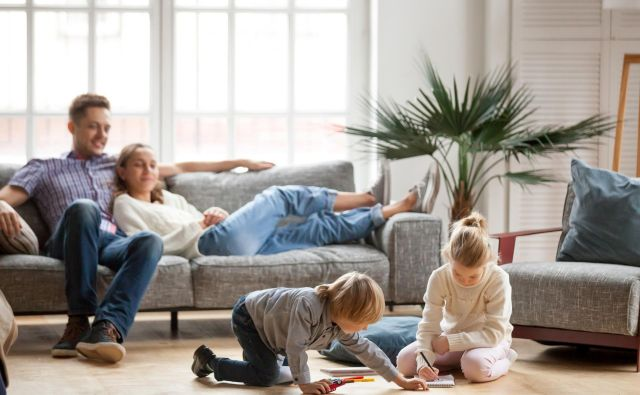 Children sister and brother playing drawing together on floor while young parents relaxing at home on sofa, little boy girl having fun, friendship between siblings, family leisure time in living room Foto Fizkes Getty Images/istockphoto