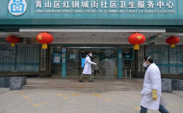 Delavec dezinficira vhod v bolnišnico v Wuhanu. FOTO: Reuters