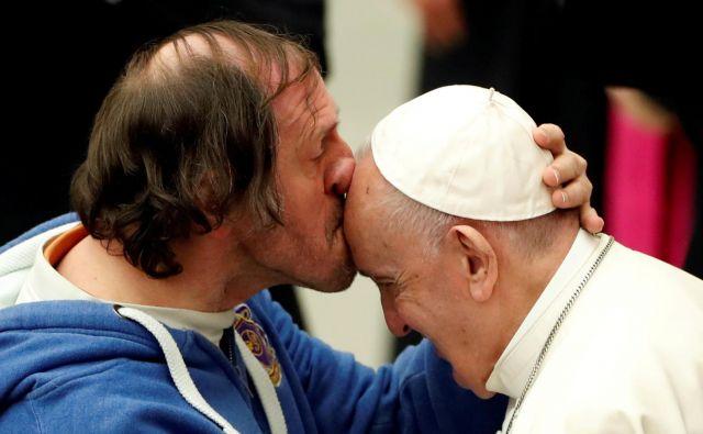 Na papeževi tedenski avdienci v Vatikanu je eden od vernikov poljubil svetega očeta na čelo. FOTO: Yara Nardi/Reuters