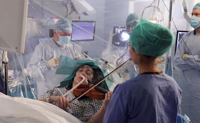 Bolnica v londonski bolnišnici King&#39;s College je med težko operacijo na možganih igrala na violino. 53-letna Dagmar Turner je leta 2013 med igranjem z orkestrom doživela epileptični napad. Diagnosticirali so ji počasi rastoči možganski maligni tumor, ki je kljub zdravljenju z radioterapijo rasel naprej, zato so ga morali odstraniti. Glasbenica se je pred zahtevnim posegom zelo bala, da ne bo mogla več igrati violine. Njen tumor se je nahajal na desni strani čelnega režnja, blizu dela, ki nadzoruje premikanje njene leve roke. Priznani nevrolog Keyoumars Ashkan, ki je prav tako glasbenik oziroma pianist, ji je zato predlagal metodo, ki sicer danes ni takšna redkost. PHOTO: KING&#39;S COLLEGE HOSPITAL/Afp<br />