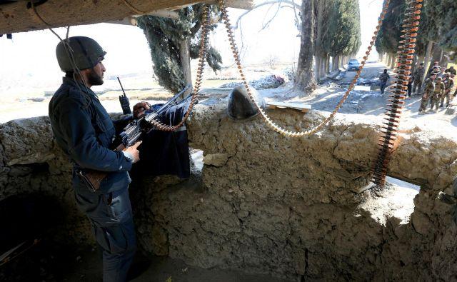 Pripadnik afganistanskih varnostnih sil v bližini mesta, kjer sta bila pred tem ubita ameriška vojaka.Foto Parwiz Parwiz Reuters
