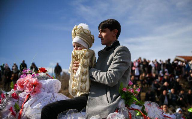 Bolgarski musliman drži svojega sina med procesijo, ki je del množične slovesnosti obrezovanja fantkov v vasi Ribnovo. FOTO: Nikolay Doychinov/Afp<br />