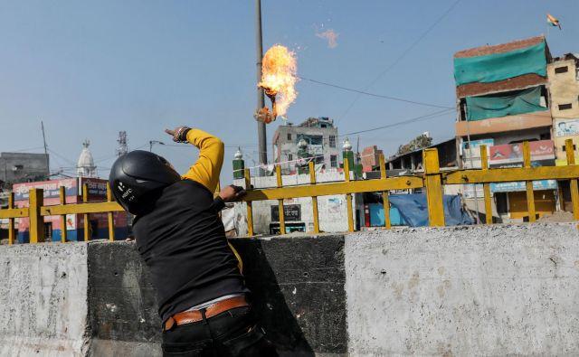 Podpornik Modijeve skrajne hindujske stranke meče bencinsko bombo na muslimansko svetišče. FOTO: Danish Siddiqui/Reuters