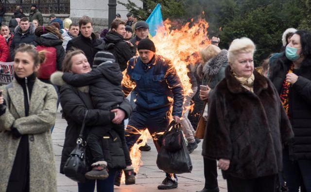 Med protestnim shodom pred predsedniškim uradom v Kijevu, se je eden od demonstrantov zažgal. FOTO: Ihor Behus/Reuters