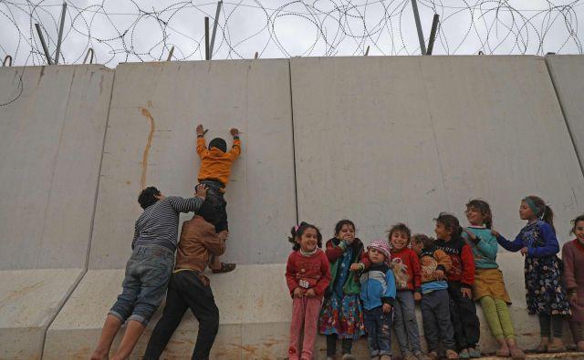 Otroški begunci, ujeti na severu Sirije, poskušajo preplezati zid, ki ga je Turčija postavila na meji, da bi preprečila prihod beguncev iz Sirije. FOTO: Aaref Watad/AFP