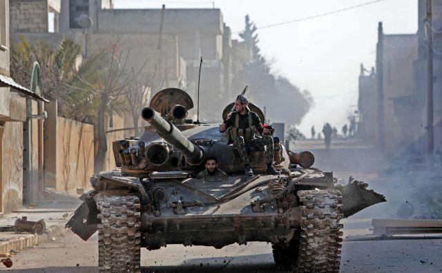 Na fotografiji sirski uporniki, nekatere od njih podpira Turčija, v strateško pomembnem mestu Saraqib. FOTO: Bakr Alkasem/AFP