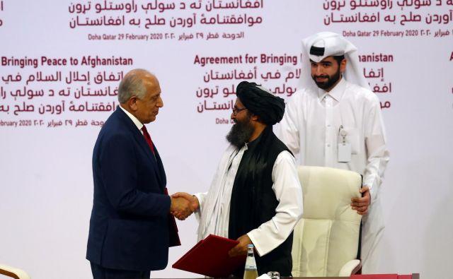 Mirovni dogovor med ZDA in talibi sta danes podpisala vodja talibske delegacije Abdul Gani Baradar in vodja pogajalcev Bele hiše Zalmay Khalilzad Ibraheem. FOTO: Al Omari/Reuters