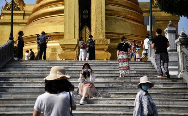 Strah pred širjenjem virusa je v številnih svetovnih znamenitostih že za polovico zmanjšal obisk in vplival na obvezno opremo obiskovalcev. Na fotografiji Kraljeva palača v Bangkoku. FOTO: AFP