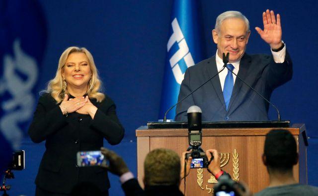 Izraelski premier Benjamin Netanjahu z ženo Saro pozdravlja svoje podpornike. FOTO: Gil Cohen-Magen/AFP